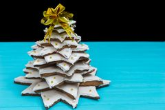 Big homemade gingerbread Christmas tree on blue wooden desk. Mockup for seasonal offers and holiday post card Royalty Free Stock Images