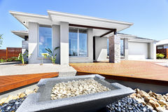 Big house and garden filled with stones. Well decorated yard and garden using stone elements in front of a modern house, closeup of a small square shape pond royalty free stock photography