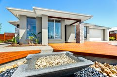 Big house and garden filled with stones. Well decorated yard and garden using stone elements in front of modern house, closeup of a small square shape pond made stock photos