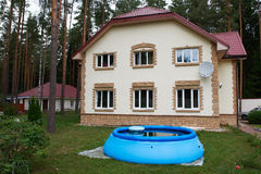 Big house out of town and an inflatable pool Royalty Free Stock Photos