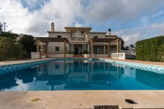 Big house with swimming pool in a cloudy day royalty free stock image