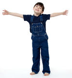 Big Hug. Adorable six year old boy in overalls with his arms stretched out to show size or invite hug royalty free stock photos