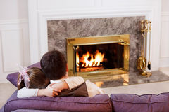 Big hug for Dad. Daughter hugs her Dad by the light of a warm fire Royalty Free Stock Photo