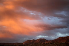 Big huge sunset clouds over the red mountains in Tucson Arizona. Desert mountain sunset. Sunset heavily saturated with color. Dramatic red sunset over the Tucson Stock Image
