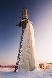 Big icicle hanging from water tower in winter. Royalty Free Stock Image