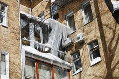 Big icicles, freezing. Big icicles, the freezing weighing on a roof and a balcony of the house in the winter and in the spring. Problem of saving of heat Royalty Free Stock Photos