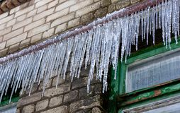Big icicles on a building wall Stock Photo