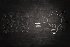 Big idea equal small ideas on chalkboard. Picture of many small lightbulbs equal big lightbulb royalty free stock images