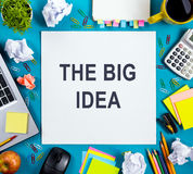 The big idea. Text words advice on office table desk with supplies, white blank note pad, cup, pen, pc, crumpled paper Stock Image