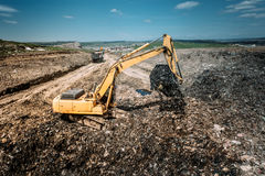 Big, Industrial city waste dump yard details - excavator doing construction works Royalty Free Stock Photo