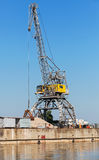 Big industrial harbor crane works on the coast Stock Photo