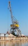 Big industrial harbor crane works on the coast Stock Photo