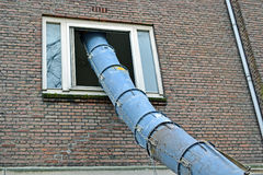 Big industrial pipe into window hole, modern construction, Stock Image
