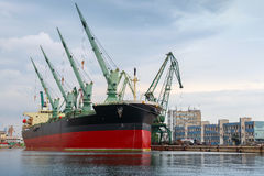 Big industrial ship with cranes is loading in port Stock Photography
