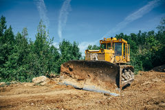 Big industrial yellow excavator on construction site. Big industrial yellow excavator or bulldozer on construction site, green trees and blue sky on foreground Royalty Free Stock Image