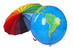 Big inflatable globe and colored umbrella isolated Royalty Free Stock Images
