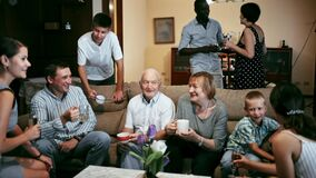 Big international family gathered together in parental home, cheerfully talking in living room
