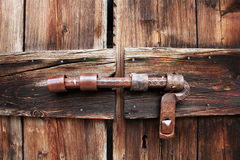 Big iron bolt. Iron padlock on an old wooden door in the rough Royalty Free Stock Photos