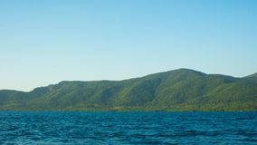 Big island with deep blue dark sea and clear sky in tropical country stock images