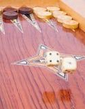 Big ivory dices fall on handmade backgammon board. Two big ivory dices falling on wooden handmade backgammon board with chips and on white background Royalty Free Stock Photo
