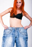 Big jeans on small woman Royalty Free Stock Photography