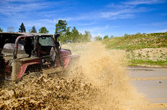 Big Jeep and a muddy splash 3. Red Jeep with over sized tires splashing mud in the mountains Stock Images
