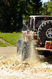 Big Jeep splashing mud in the mountains. Red Jeep with over sized tires splashing mud in the Colorado mountains Royalty Free Stock Images