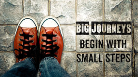 Big journeys begin with small steps, Inspiration quote. Shoes on street
