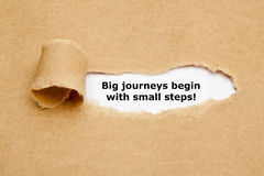 Big journeys begin with small steps. The motivational quote Big journeys begin with small steps, appearing behind torn brown paper stock photography