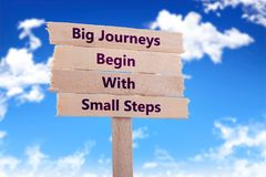 Big journeys begin with small steps. Wooden sign with blue sky background stock photography