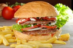 Big juicy double burger with french fries Royalty Free Stock Photos