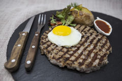 Big juicy grilled steak marbled beef with egg baked potatoes with barbecue sauce. Served on a stone plate with a fork and spoon on Royalty Free Stock Image