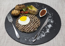 Big juicy grilled steak marbled beef with egg baked potatoes with barbecue sauce. Served on a stone plate with a fork and spoon on Stock Photography