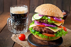 Big juicy hamburger with vegetables and beef on a wooden background Royalty Free Stock Photo