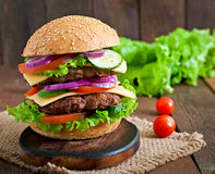 Big juicy hamburger with vegetables  on a wooden background Royalty Free Stock Photo