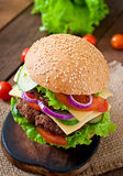 Big juicy hamburger with vegetables  on a wooden background Royalty Free Stock Images