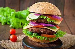 Big juicy hamburger with vegetables  on a wooden background Stock Photos