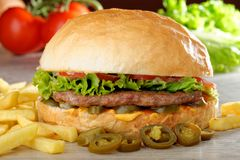 Big juicy Mexican burger with spicy jalapenos. Nacho cheese and a chips Royalty Free Stock Photo