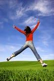 Big Jump. Woman making a big jump on a beautiful green meadow Stock Photo