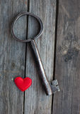 Big key and red heart on wooden rustic table Royalty Free Stock Photography
