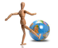 Big kick. Wooden mannequin big kick the world royalty free stock images