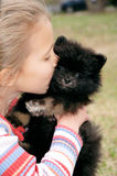Big Kiss. Little girl gives her pomeranian a big smooch to the face Royalty Free Stock Photo