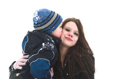 Big kiss for mommy. A child kisses his mother as they play in the snow stock photos