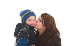 A big kiss from mommy. A mother and son have the time of their life playing in the snow royalty free stock image