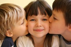 Big Kisses for Sister. Two brothers give their sister a big kiss on both cheeks Royalty Free Stock Photo