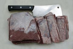 Kitchen knife and beef meat cut into big slices on white cutting board. royalty free stock images