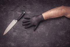 Big Knife and Male Hands with Black Latex Gloves. On Dark Background royalty free stock images