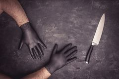 Big Knife and Male Hands with Black Latex Gloves. On Dark Background royalty free stock photos