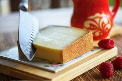 Gruyere cheese, knife, jug and raspberry. Big knife slices hard and spicy gruyere cheese on wooden kitchen board, one raspberry and red jug Royalty Free Stock Images