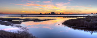 Big Lagoon Winter Sunset Panorama. A colorful sunset reflected in the inlet at Big lagoon State Park, with Perdido Key, Florida silhoetted in the background stock photography